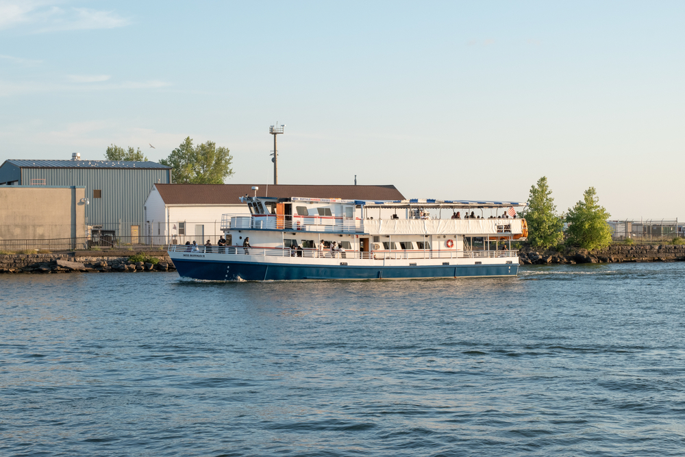 A tour boat sails around Buffalo New York while Ellicott Development lists the best boat tours in Buffalo