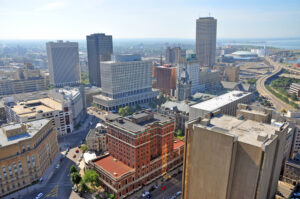 An aerial photo of downtown Buffalo NY on a sunny day as Ellicott Development lists properties for sale in the area